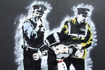 graffiti stencil of two gardai arresting the monopoly man