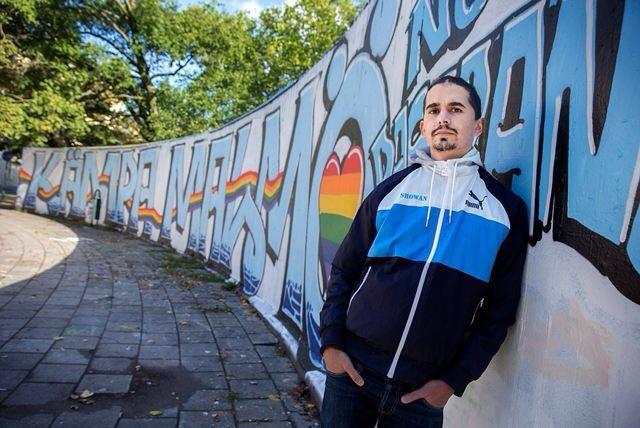 Showans Shattak leaning against a mural