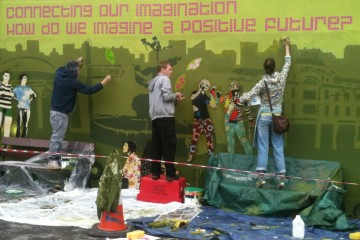 Young people painting a mural. It reads 'Connecting our imagination, how do we imagine a positive future?'