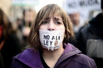Woman protesting against the ley Mordaza, wearing a gag