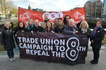 Members of the trade union campaign to repeal the 8th amendment stand with their banner