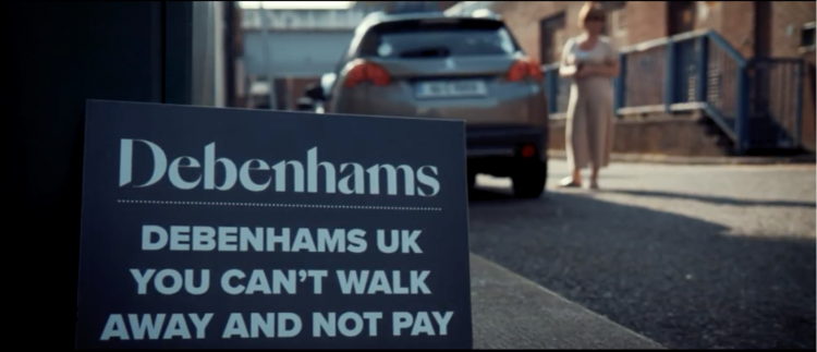 "A placard at the Cork demonstration which reads ""Demenhams UK you can't walk awayac and not pay"""