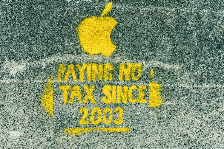 "Photo of a spray painted image no Dublin street. There is an image of the Apple company logo and text saying ""Paying no tax since 2003"""